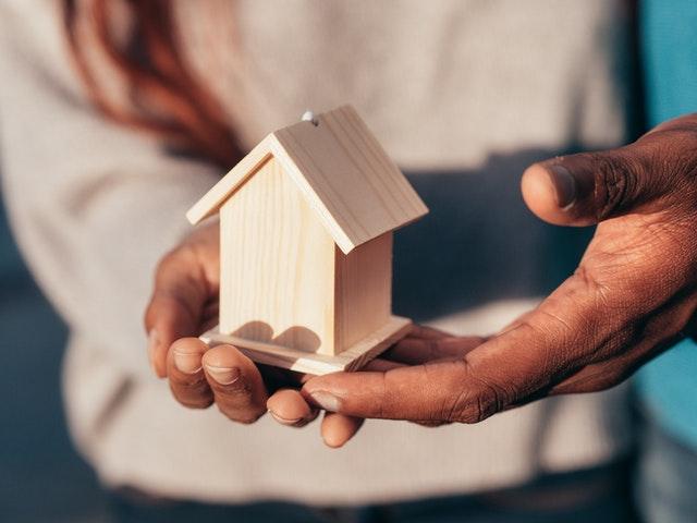 drewniany domek w rękach pary