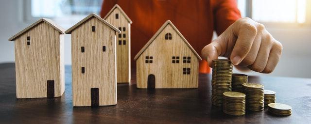 drewniane domki i monety na stole