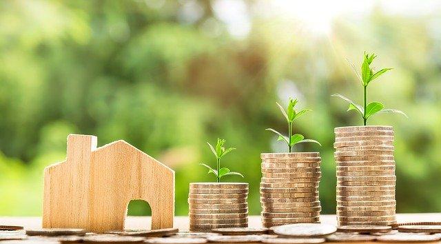 drewniany domek i stosy monet