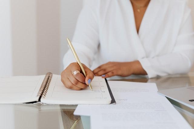 kobieta zapisuje coś w kalendarzu