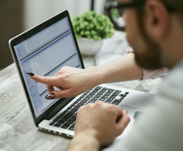 kobieta pokazuje liczby palcem na ekranie laptopa